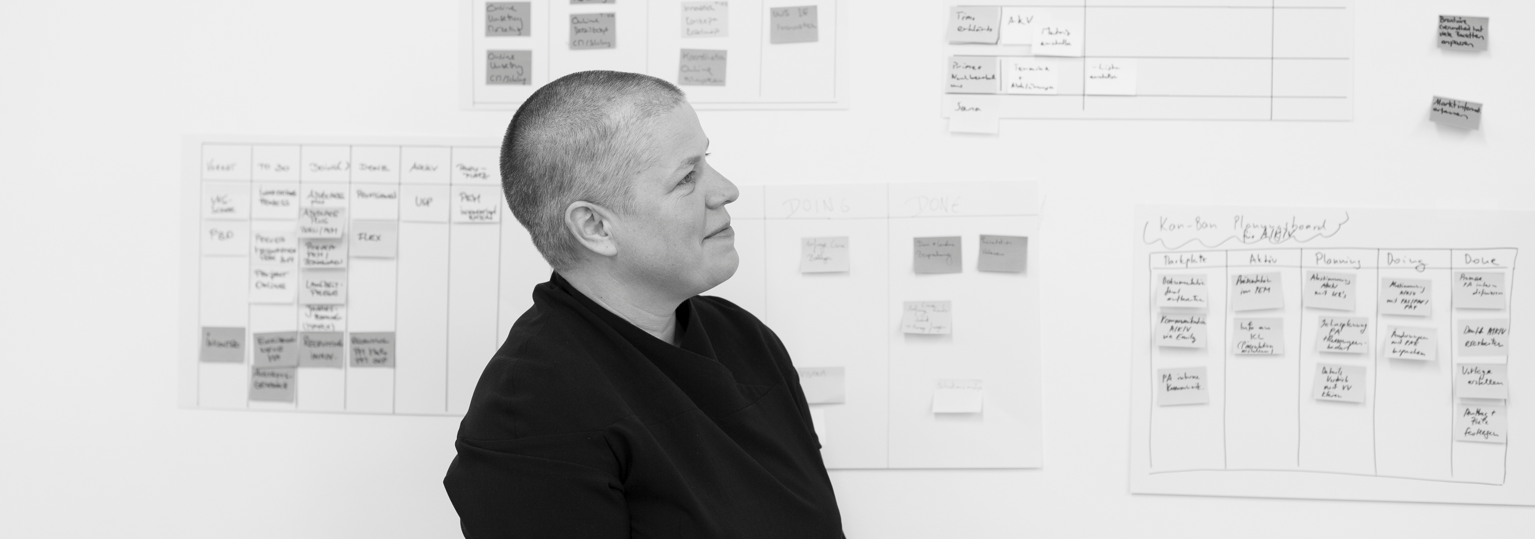 Black and white image of lady with short hair looking at a white board covered in post it notes