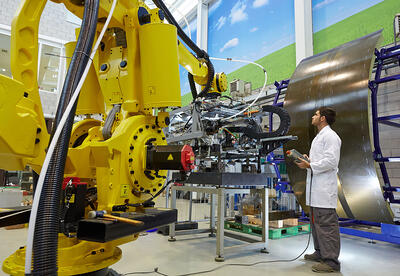 man in lab jacket operating large yellow robotic arm
